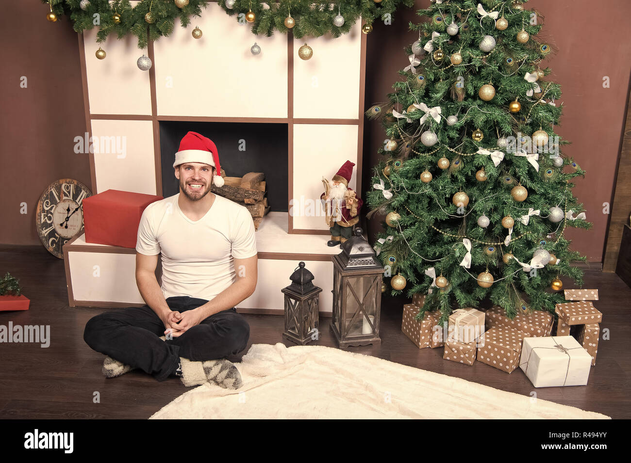 7a4542bcfbe3e Man in santa hat smile at fireplace. Macho sit at Christmas tree with present  boxes. xmas and new year room interior. Time to celebrate concept. Happy