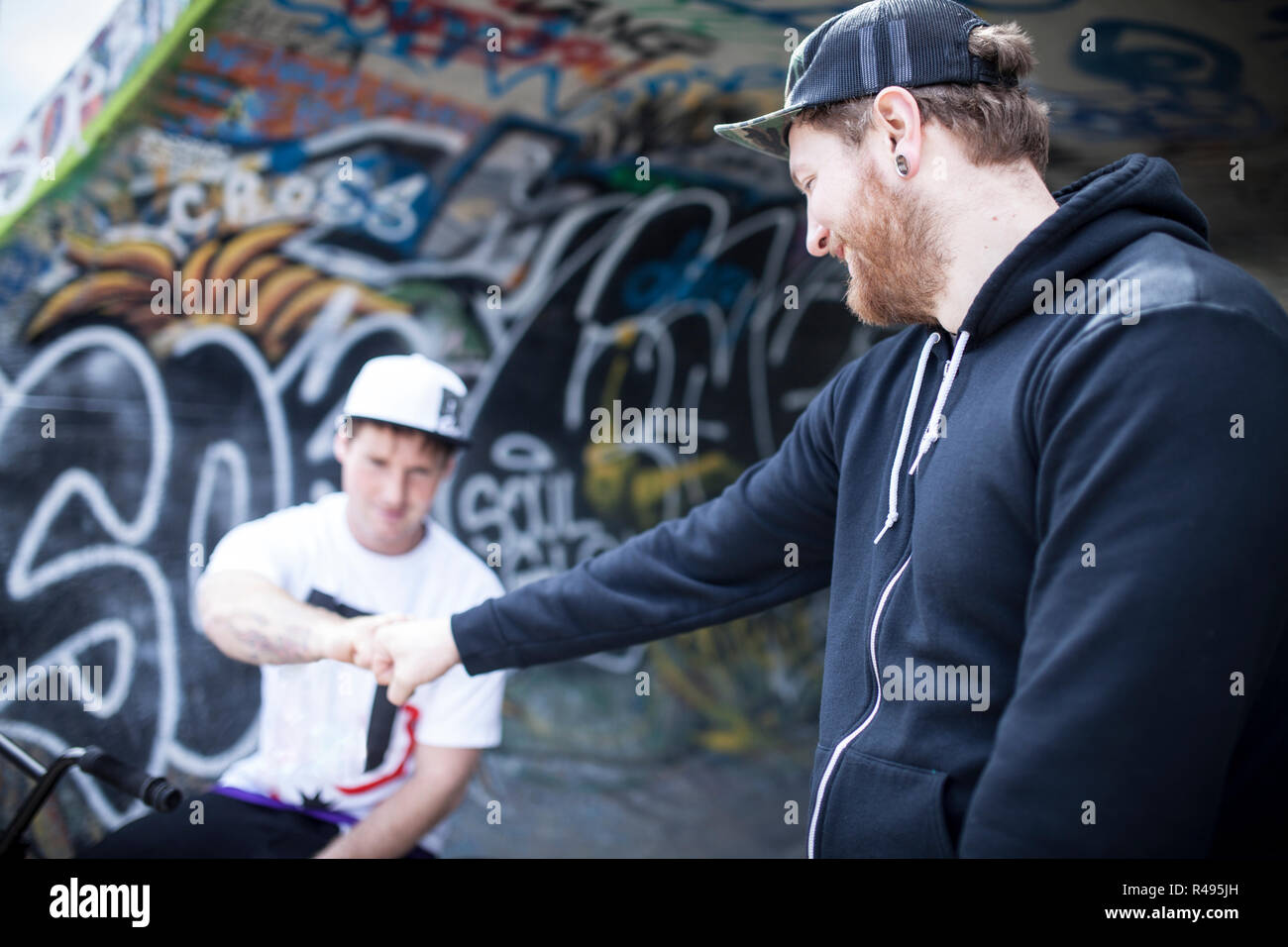 Two buddies bmxing and giving eachother a handshake in concrete ramps Stock Photo