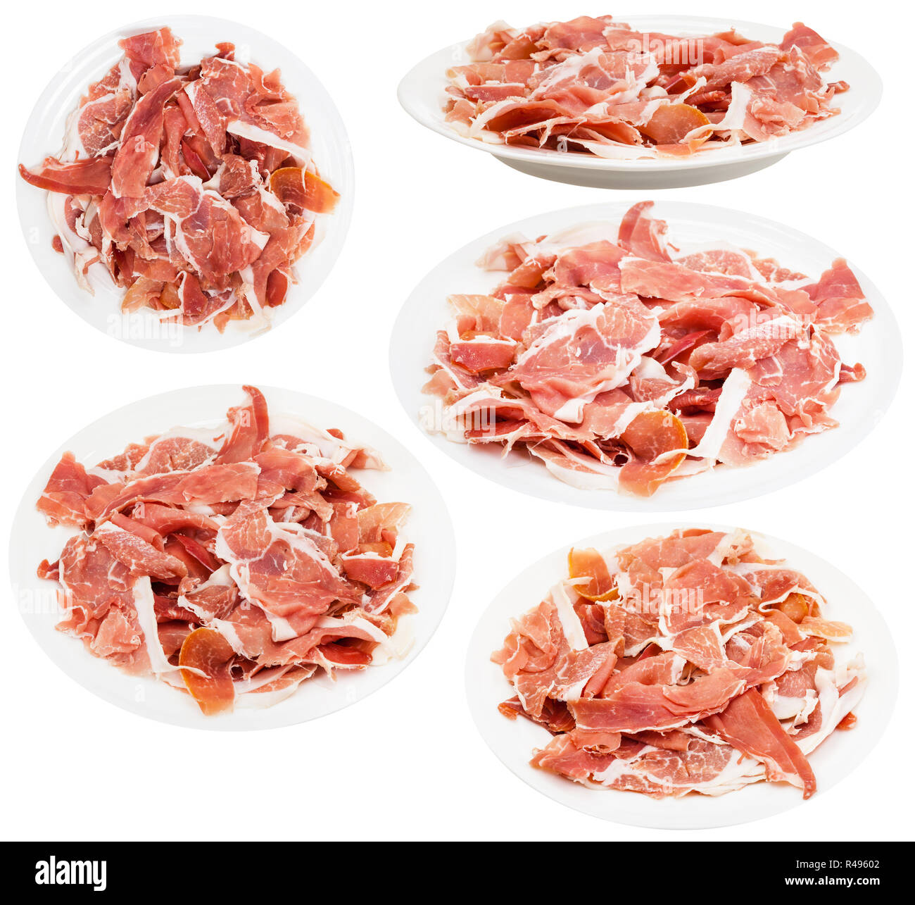 set of plates with slaced dry-cured ham isolated - Stock Image