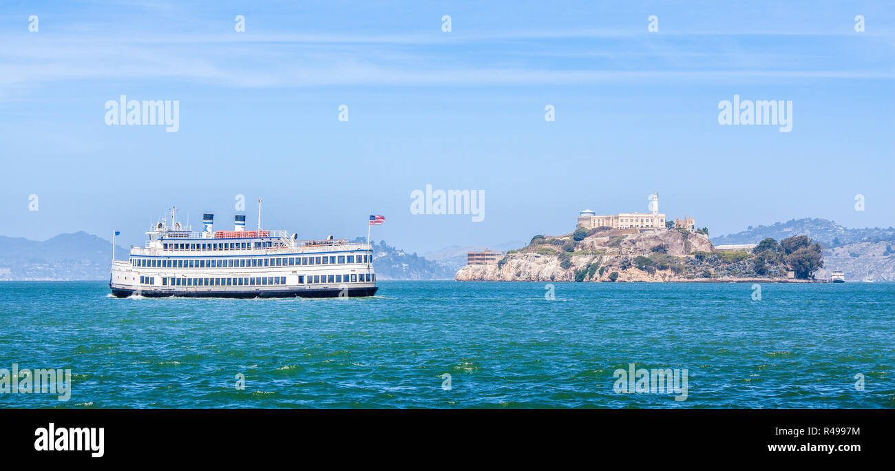 Famous Alcatraz Island with traditional historic excursion boat on a beautiful sunny day with blue sky in summer, San Francisco, California, USA - Stock Image