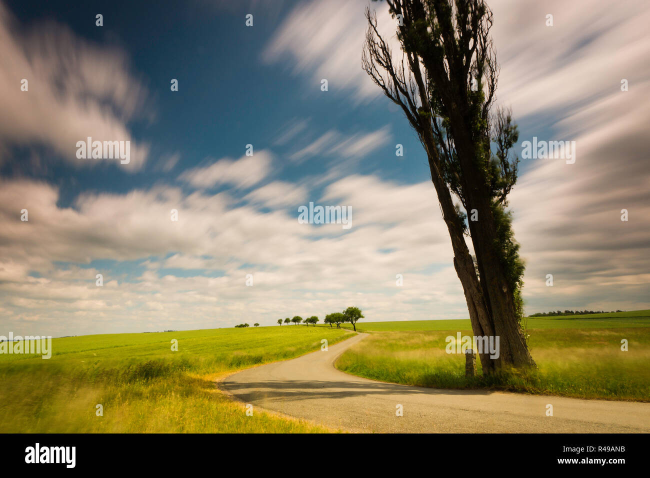 landscape in summer and clouds pulling in a long exposure on the way to the horizon Stock Photo