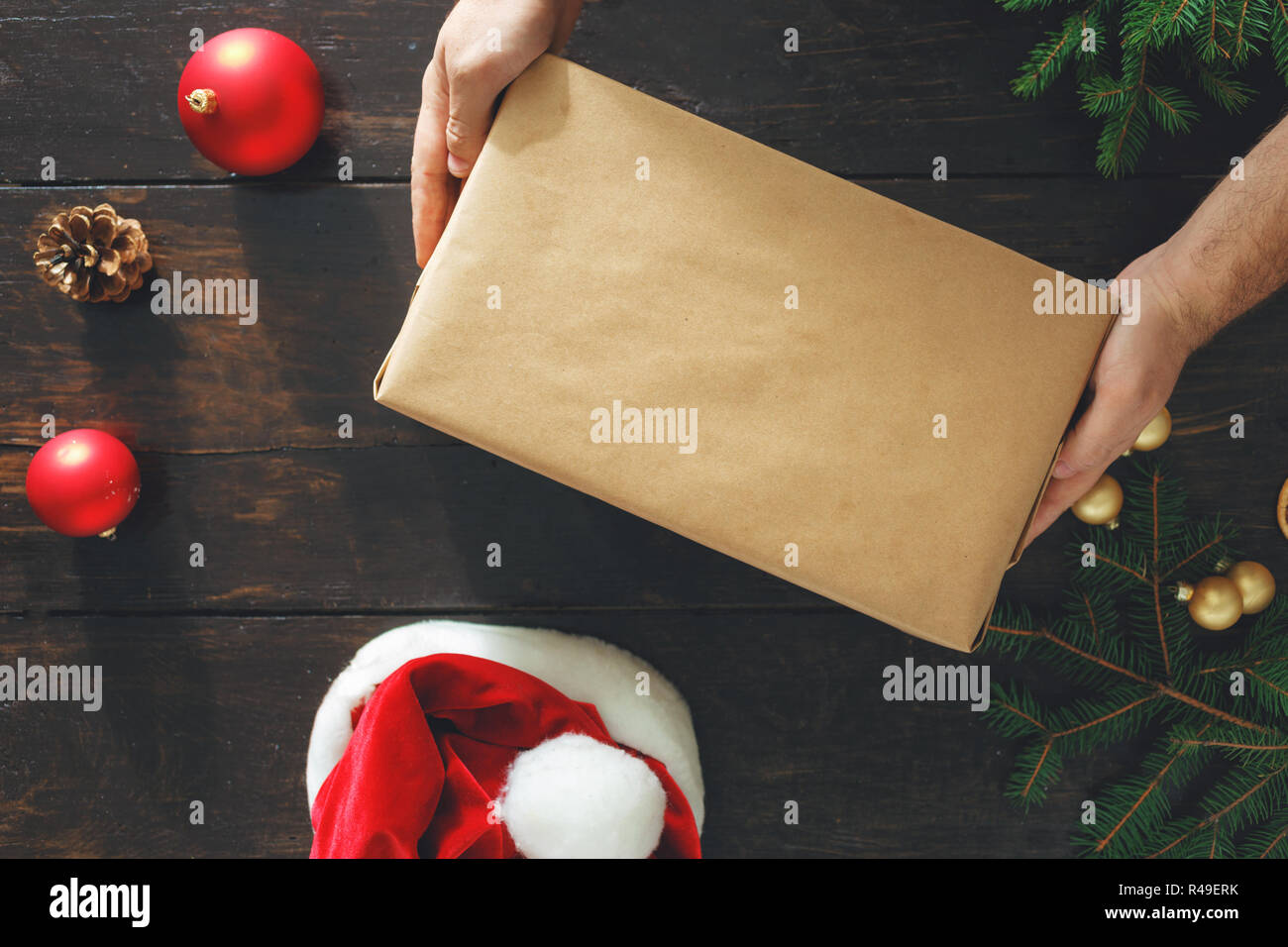 a7228b76e2 Male hands holding big box christmas present on wooden table top view.  Rustic Christmas background. Wrapping presents background