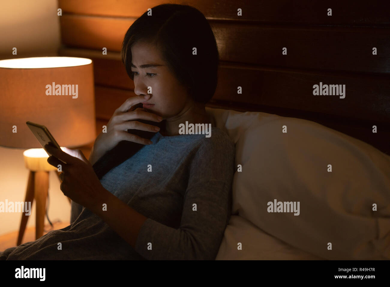 shocked woman finding bad news in a smart phone - Stock Image