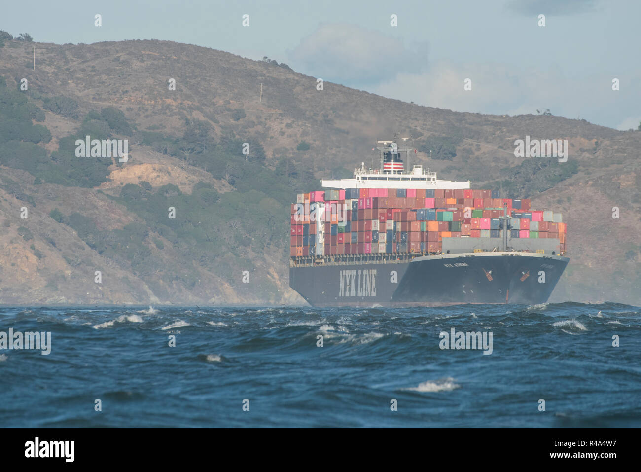 A cargo ship fully loaded with shipping containers traverses the San Francisco Bay. Stock Photo