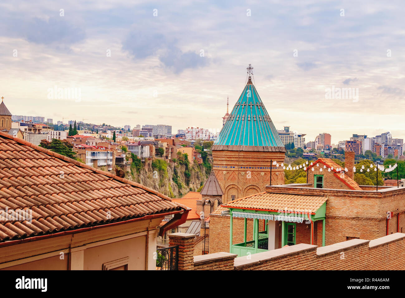 Sky over the Tbilisi Old Town neighborhood with a view on church tower and vivid red brick houses with their rooftops. Tbilisi, Georgia. Stock Photo