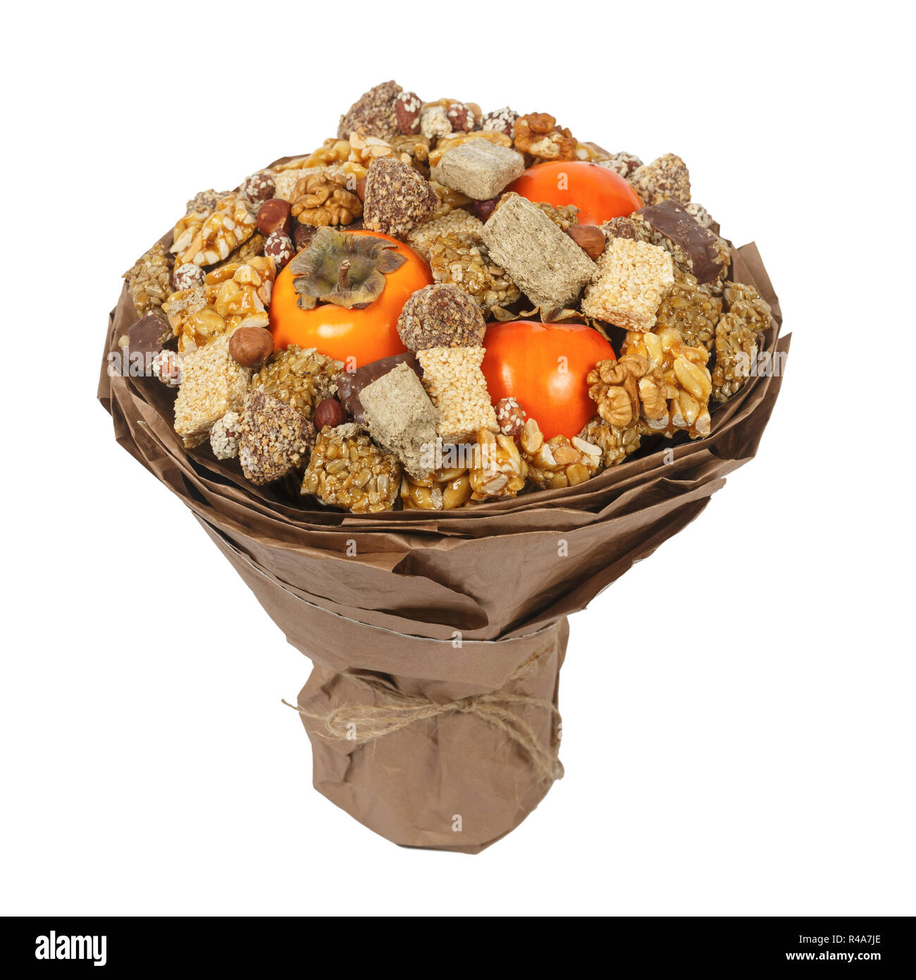 Halva, sesame snaps, nuts, chocolates and persimmons, decorated in the form of a gift bouquet on a white background - Stock Image