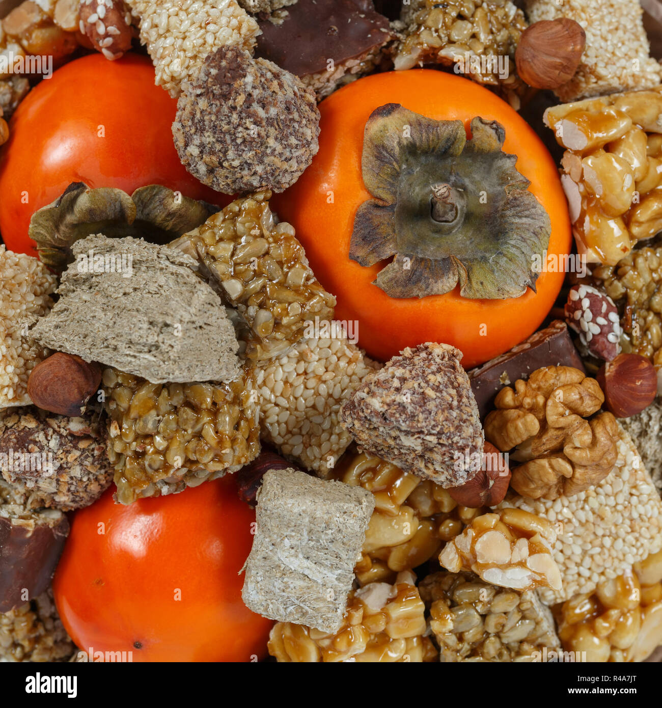 Halva, sesame snaps, nuts, chocolates and persimmons close-up as background or backdrop - Stock Image