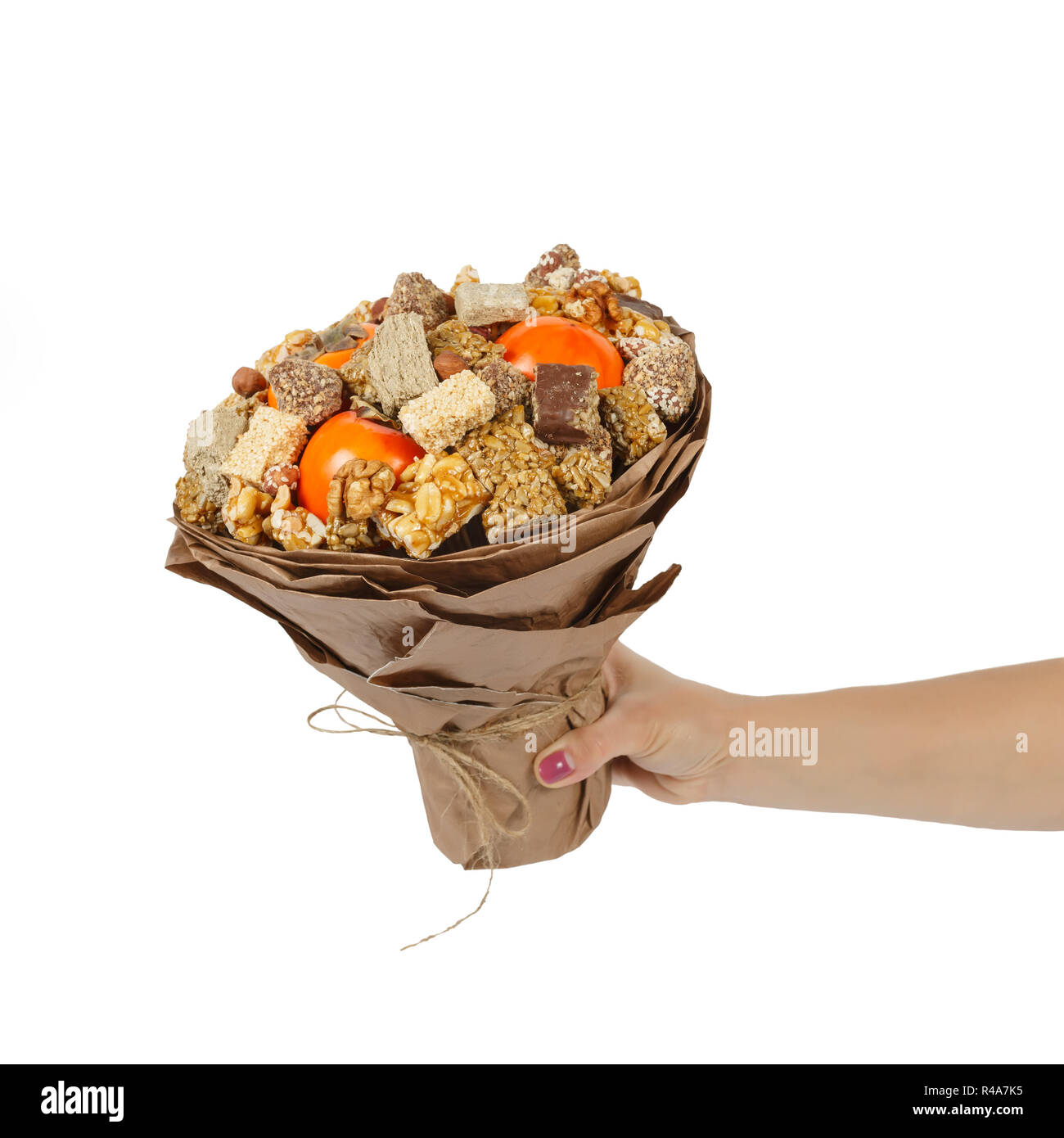 Female hand holds an original bouquet consisting of oriental sweets - halva, sesame snaps, nuts, chocolates and persimmons - Stock Image