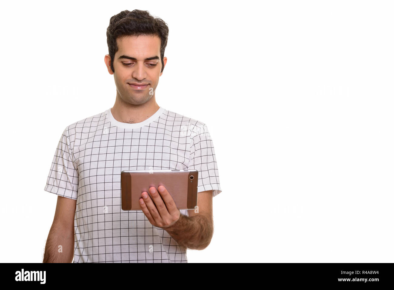 Portrait of young Persian man holding digital tablet - Stock Image