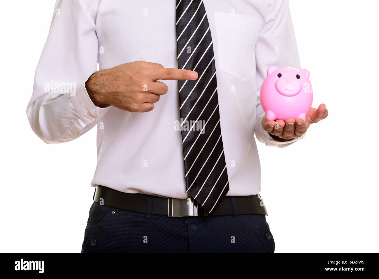 Young businessman holding piggy bank and pointing finger - Stock Image