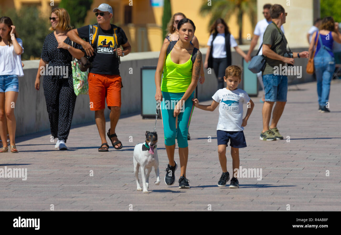 Mother and son with sports clothes walk with their pet on a summer day with people behind them. - Stock Image