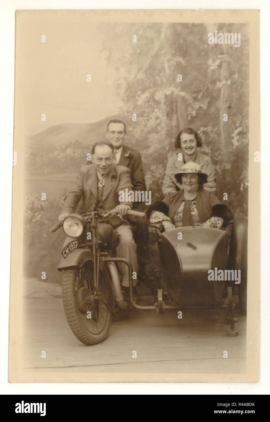 Studio portrait postcard / greetings card of happy holiday makers posing on a motorbike and sidecar prop, studio of Charles Howell, Blackpool, Lancashire, U.K. 1937 - Stock Image