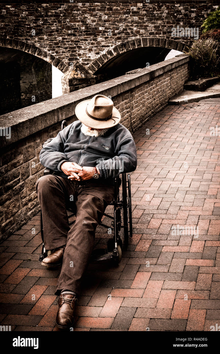 A gentleman enjoys an afternoon nap in his wheelchair. - Stock Image