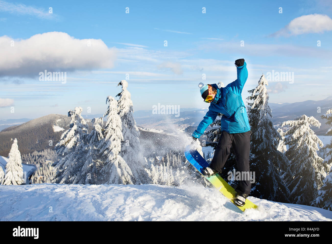 Snowboarder doing tricks at ski resort. Rider performing jump with his snowboard near forest on backcountry freeride or freestyle session in colorful fashionable outfit. Copyspace area. Powder in air. - Stock Image