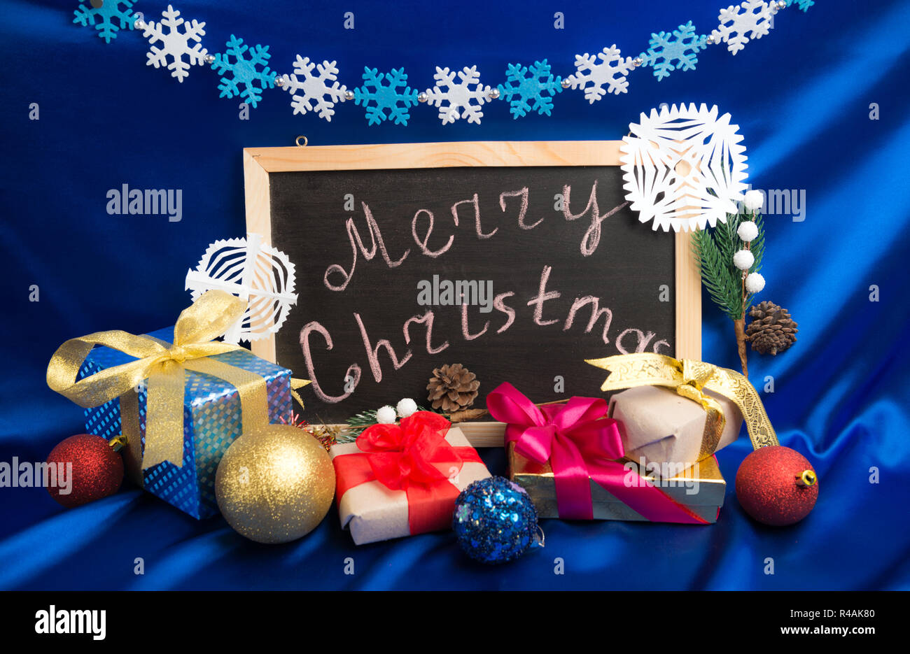 Christmas greeting at chalkboard around gift boxes and evergreen decorations on blue silk background - Stock Image