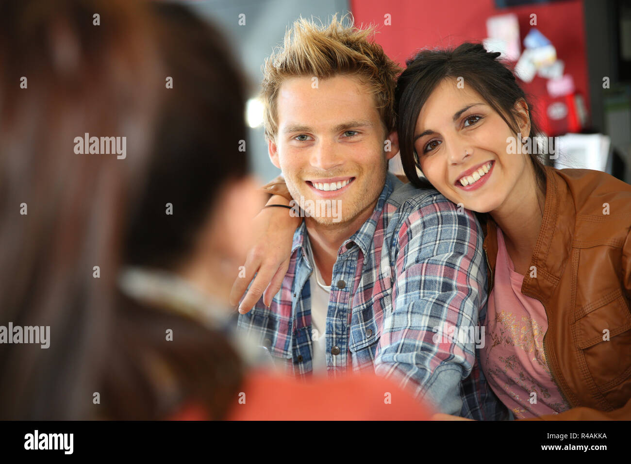 Couple gathering with friends at lunch time - Stock Image