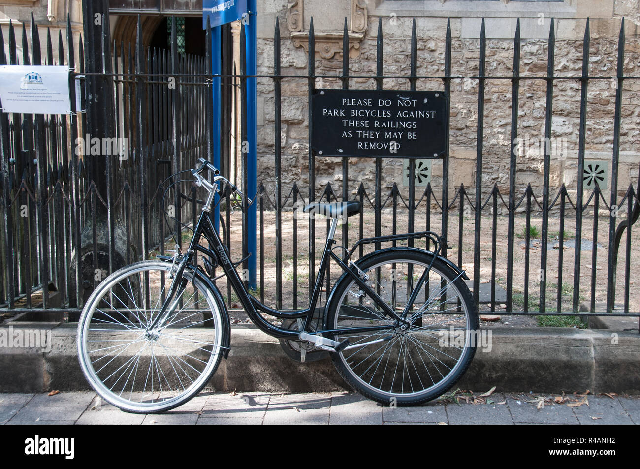 Bicycle leant against 'no parking' sign on railings - Stock Image