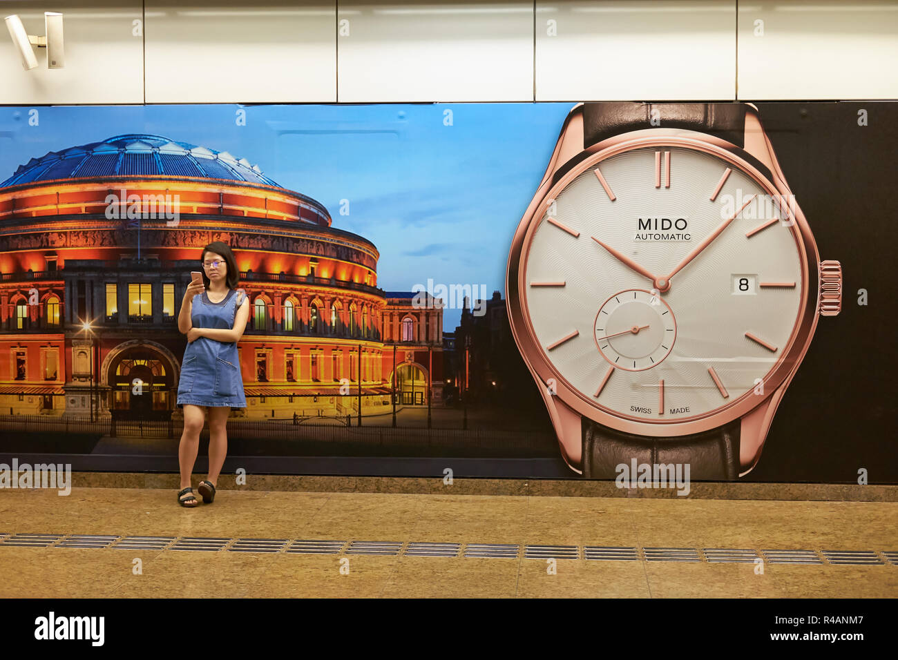 A girls busy with her mobile phone in front of a watch advertisement in Chinatown MRT station in Singapore - Stock Image