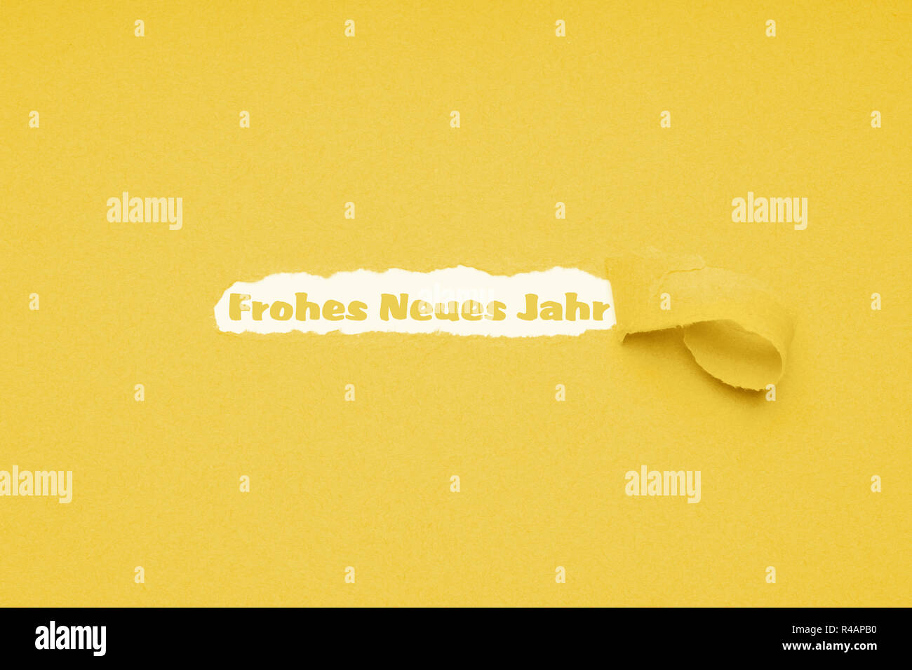 Frohes neues Jahr means happy new year in German - text seen through hole ripped in yellow paper background - Stock Image