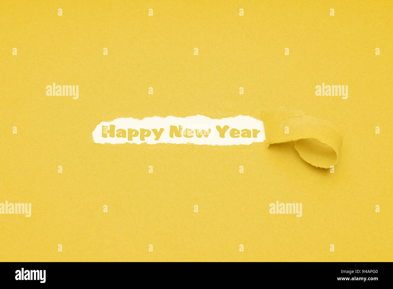 happy new year text seen through hole ripped in yellow paper background - Stock Image