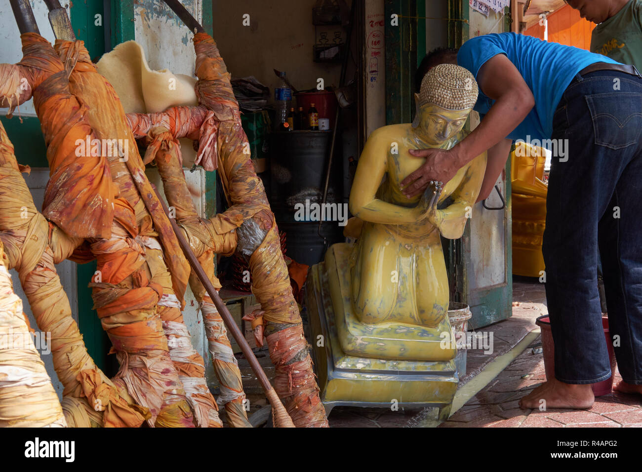 A workshop manufacturing Buddhist statues in Bamrung Muang Road, Bangkok, Thailand, a figure being readied for some final touches - Stock Image
