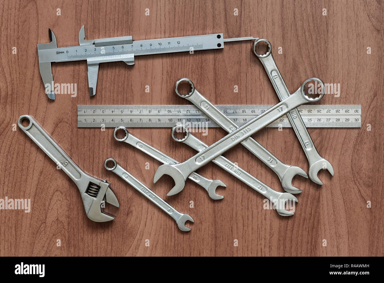Set of wrenches, caliper, ruler and adjustable wrench on a wooden table. View from above - Stock Image