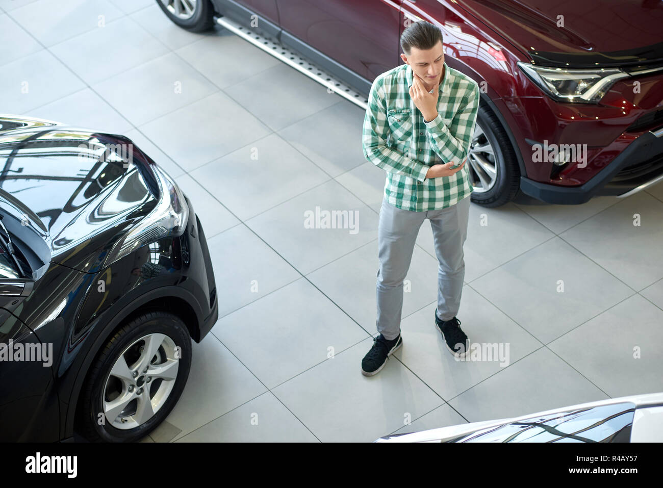 One Owner Car Guy >> Young Man Standing Between Black And Dark Red Cars Guy In Checkered