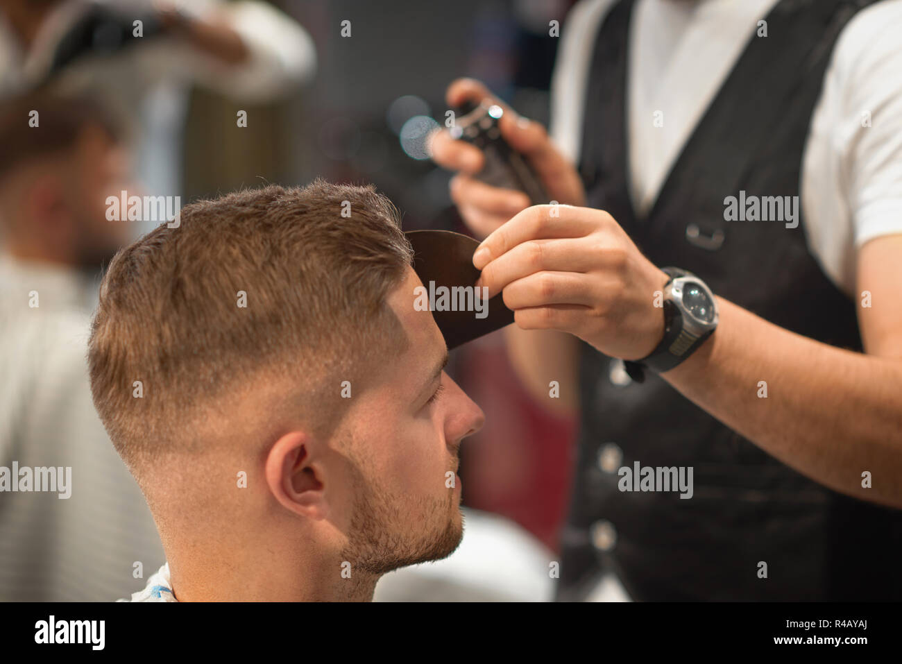 Selective focus of young man sitting in chair during procedure of hairstyling in barber shop. Qualified barber fixating hair of customer with hair spray. Concept of trendy hairdressing.  - Stock Image