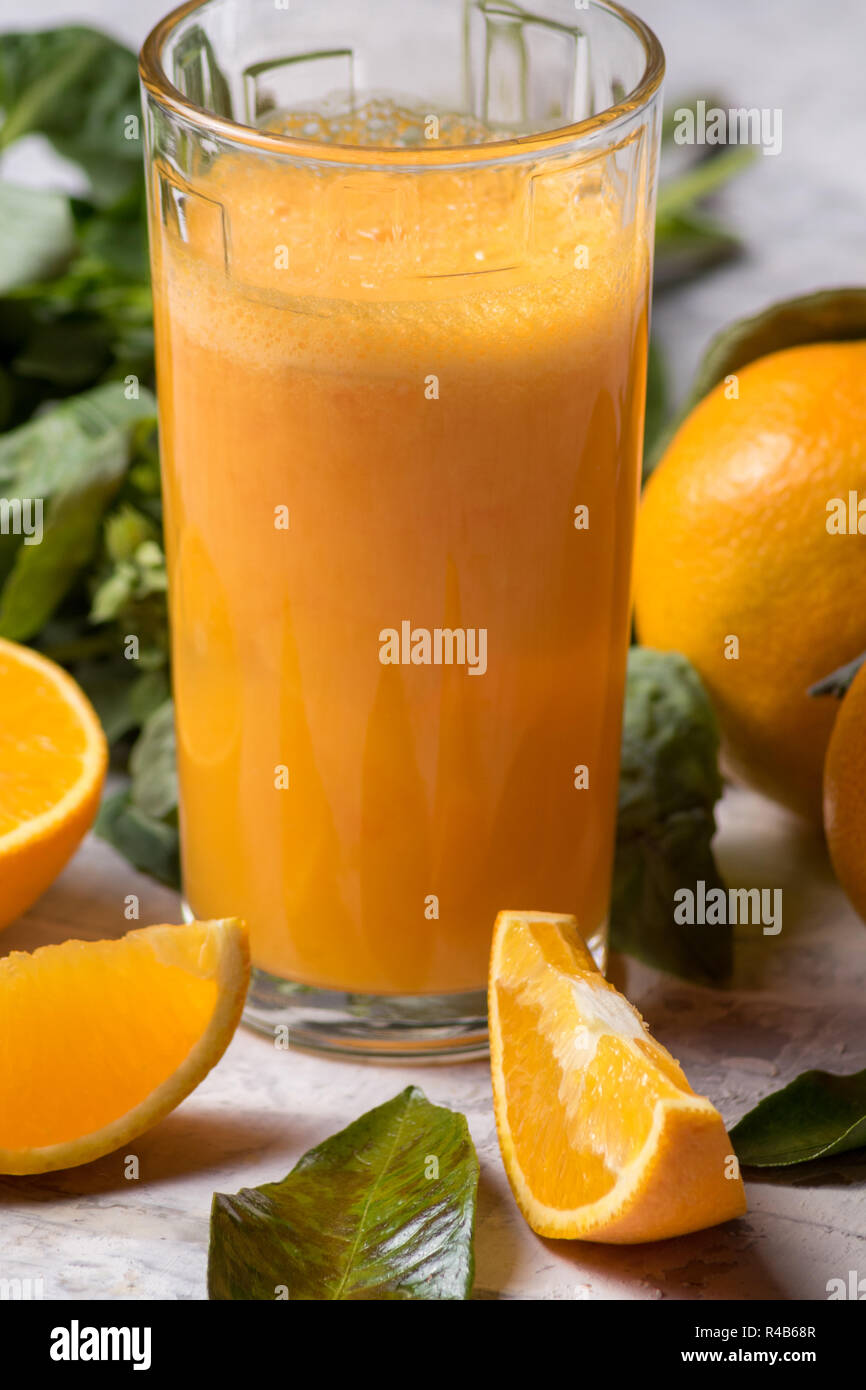 Orange juice in a glass and ripe mandarin or tangerine fruit with green leaves, over white background. - Stock Image