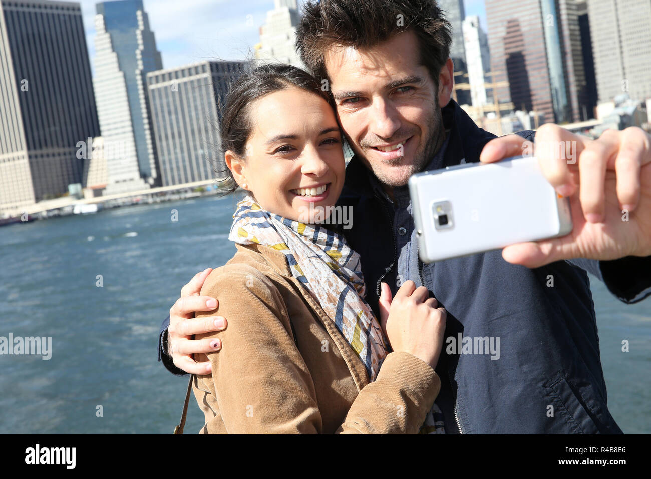 Couple taking picture with Manhattan skyline in background Stock Photo