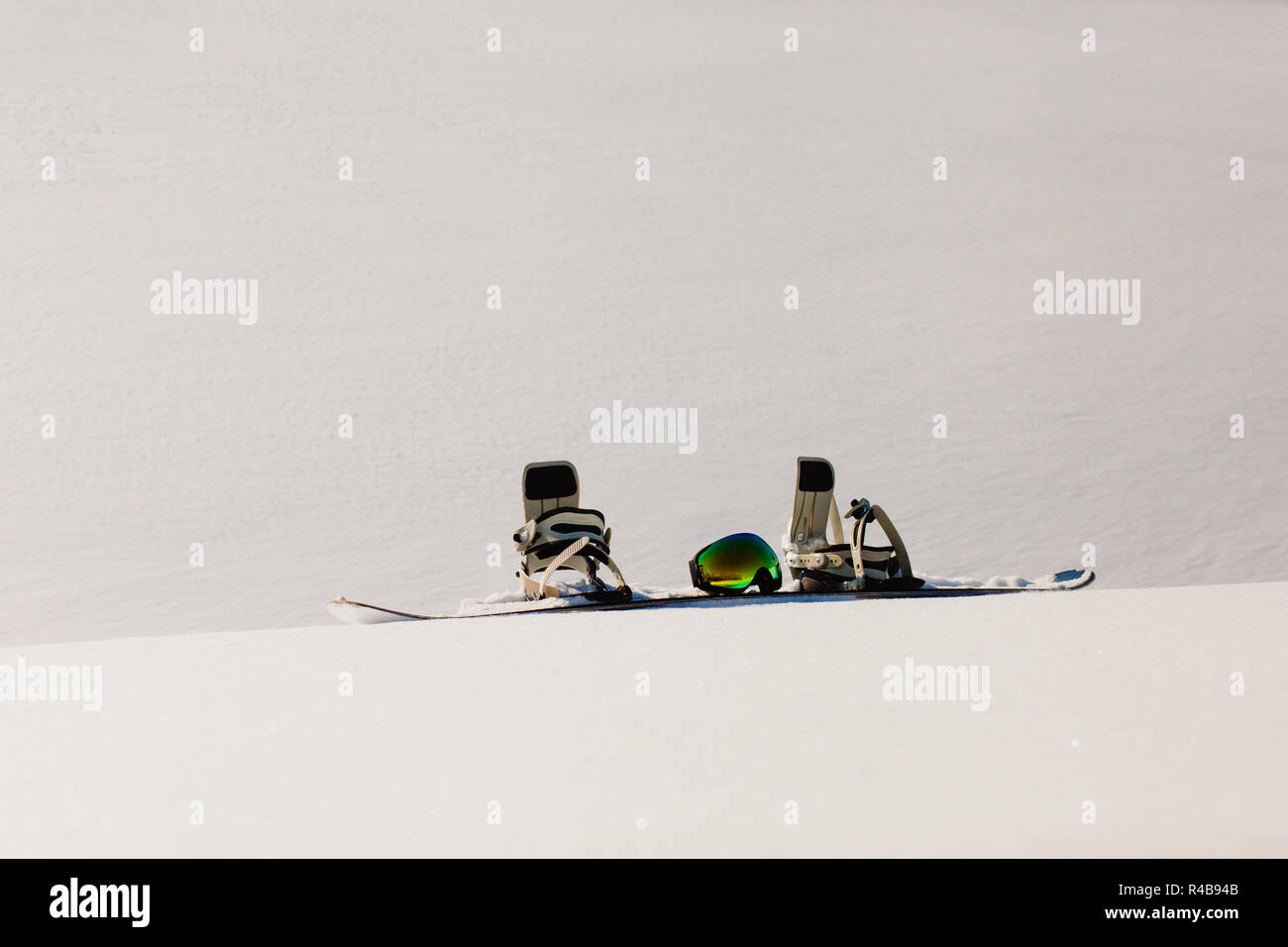 Snowboard and ski googles laying on a snow near the freeride slope - Stock Image