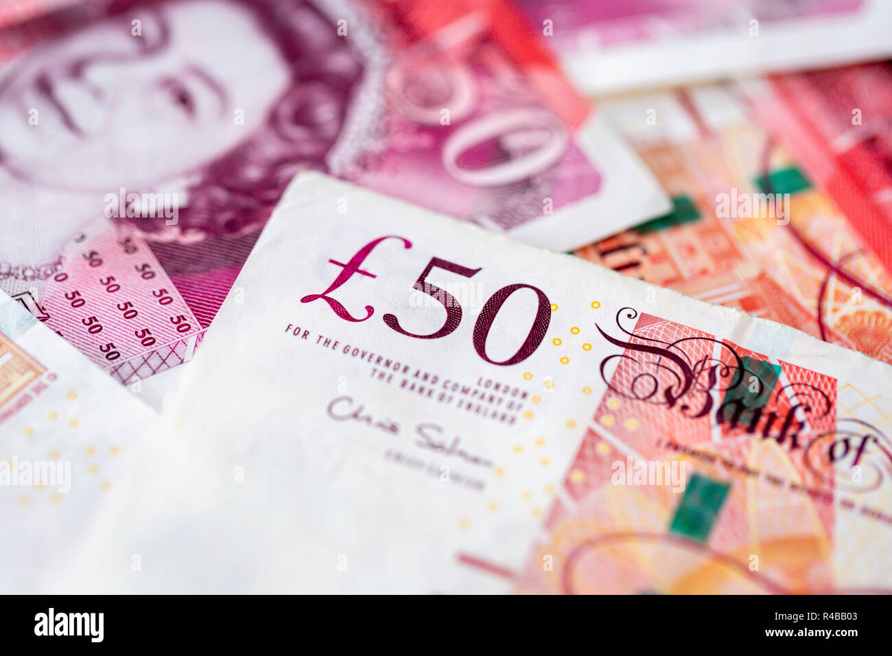 Background of a pile of fifty pound sterling bank notes - Stock Image