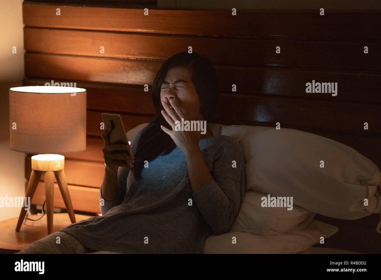 sleepy young girl using mobile phone - Stock Image