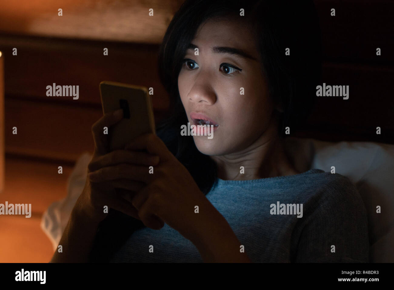 shocked girl looking at her smartphone - Stock Image
