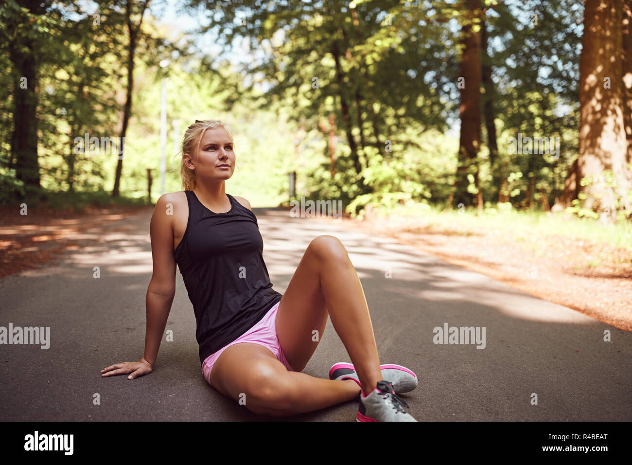 Fit young blonde woman in sportswear sitting on a path in a forest taking a break from her run Stock Photo
