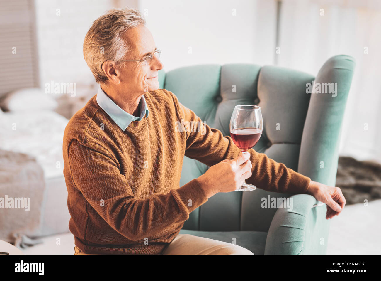 Drinking wine. Loving husband feeling respected while drinking tasty wine with his caring family - Stock Image