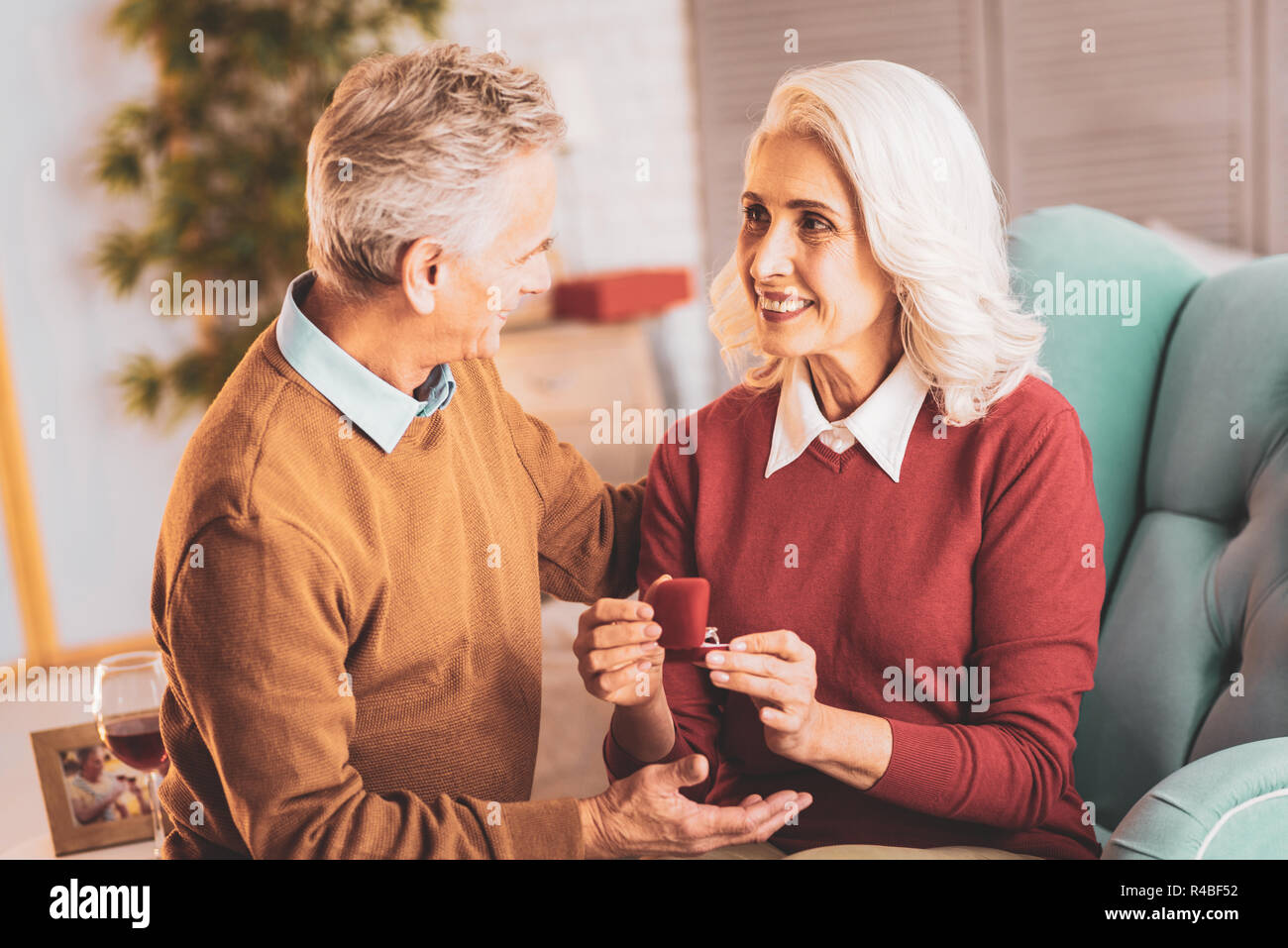 Caring husband. Caring elderly husband feeling respected while hugging his beautiful smiling wife Stock Photo