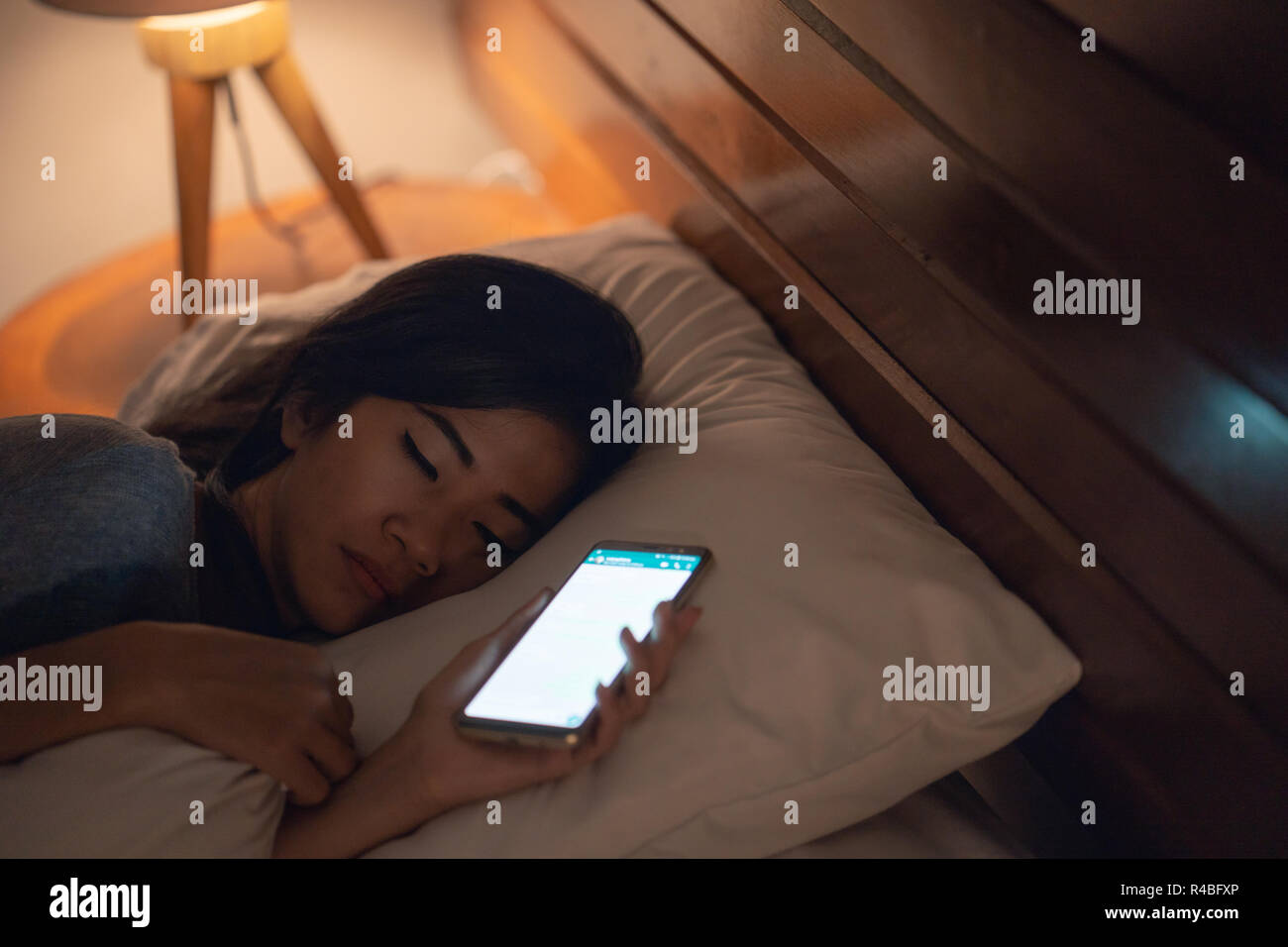 woman fell asleep after using mobile phone - Stock Image