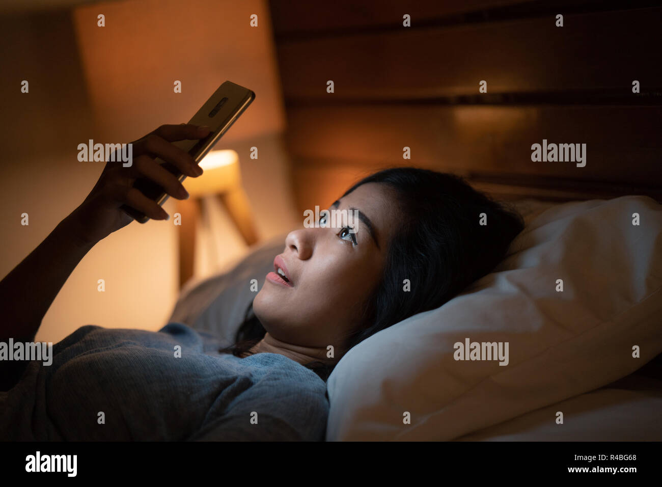 woman with mobile phone at home - Stock Image
