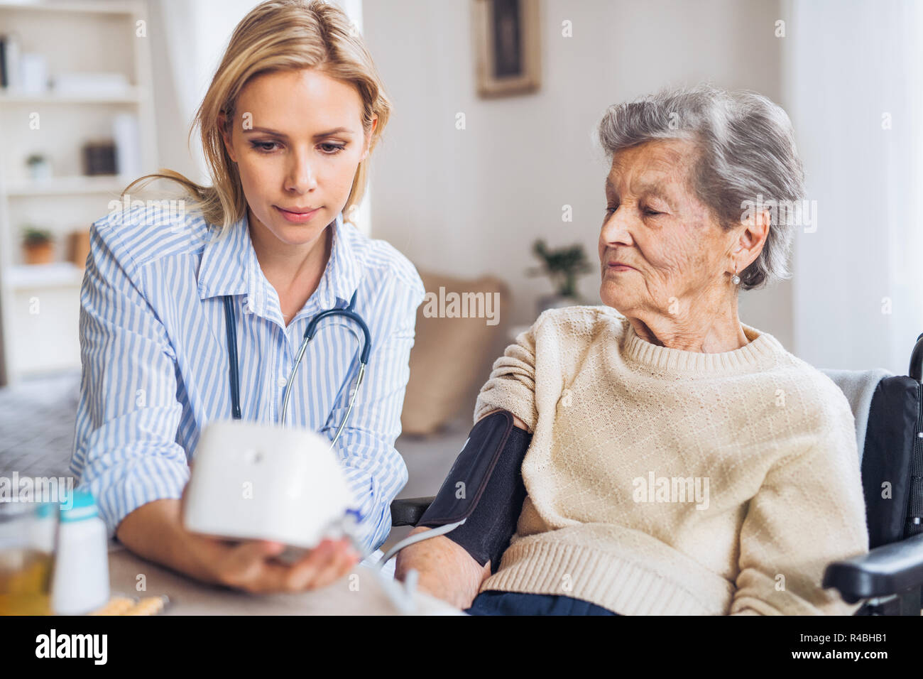 a health visitor measuring a blood pressure of a senior woman at rh alamy com woman at home bread pudding woman at home alone