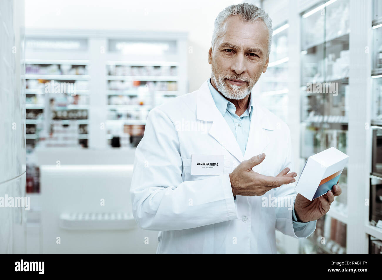 I recommend. Handsome gray-haired man demonstrating medicine while looking at camera - Stock Image