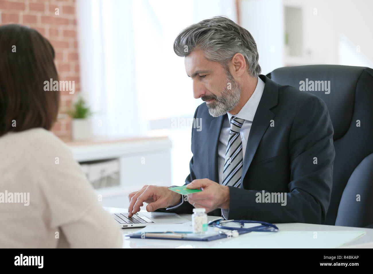 Patient giving social security card to doctor - Stock Image