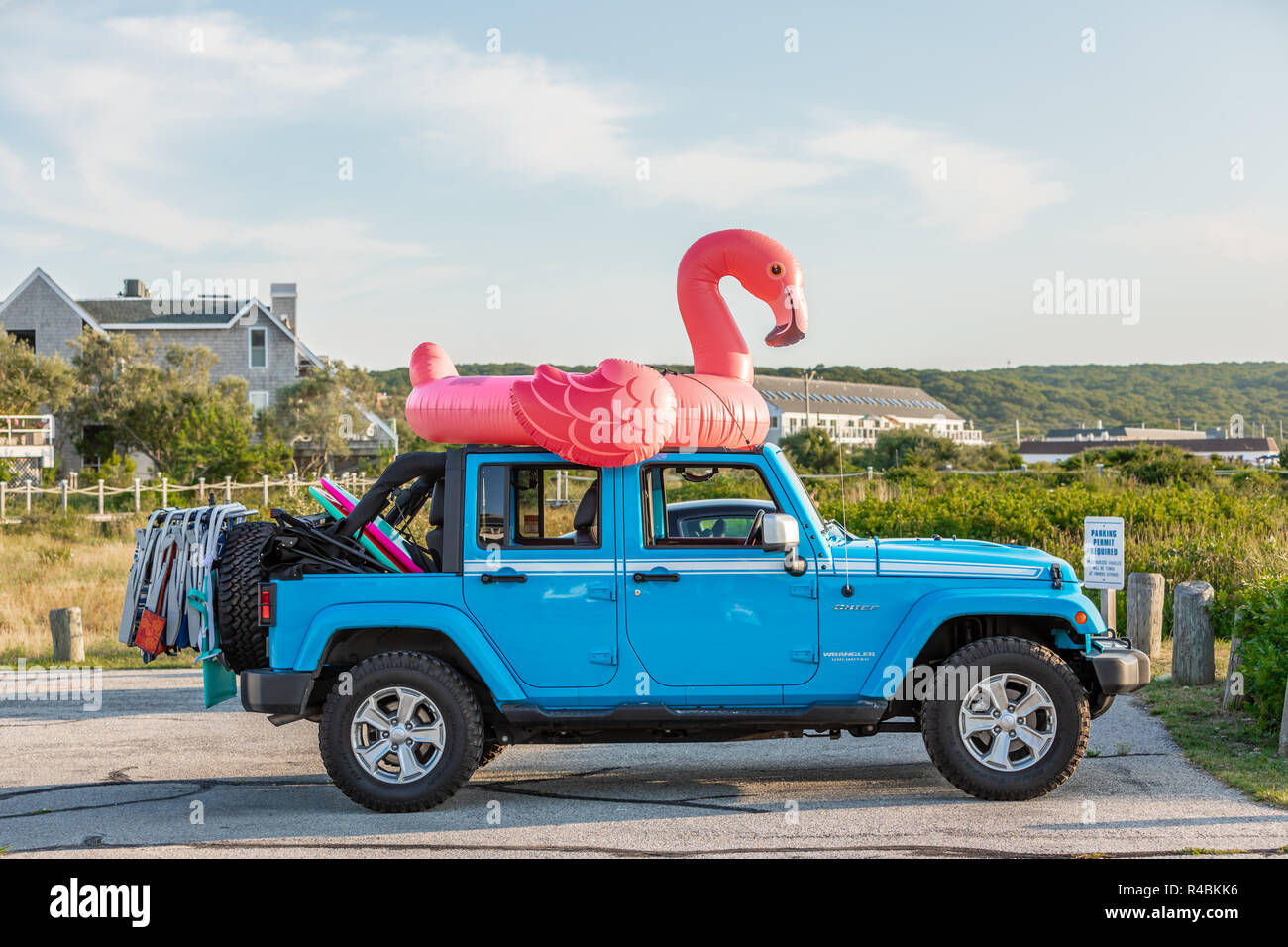 Blue jeep with a pink flamingo on top - Stock Image