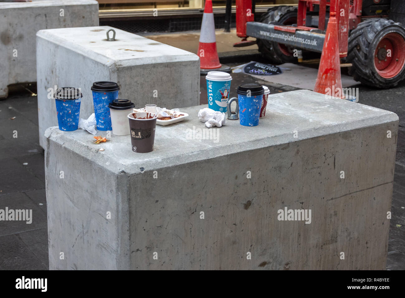 Discarded festive costa disposable cups and food wrappings left as litter on a concrete block in front of cones and machinery from building work - Stock Image