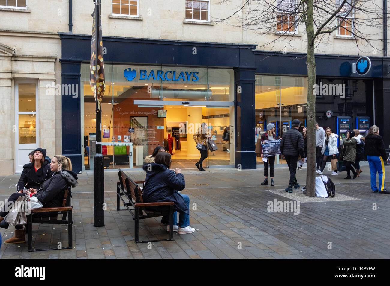 Barclays Bank branch in Southgate shopping center Bath UK with people walking past, sitting on seating outside and a small anti barclays protest - Stock Image