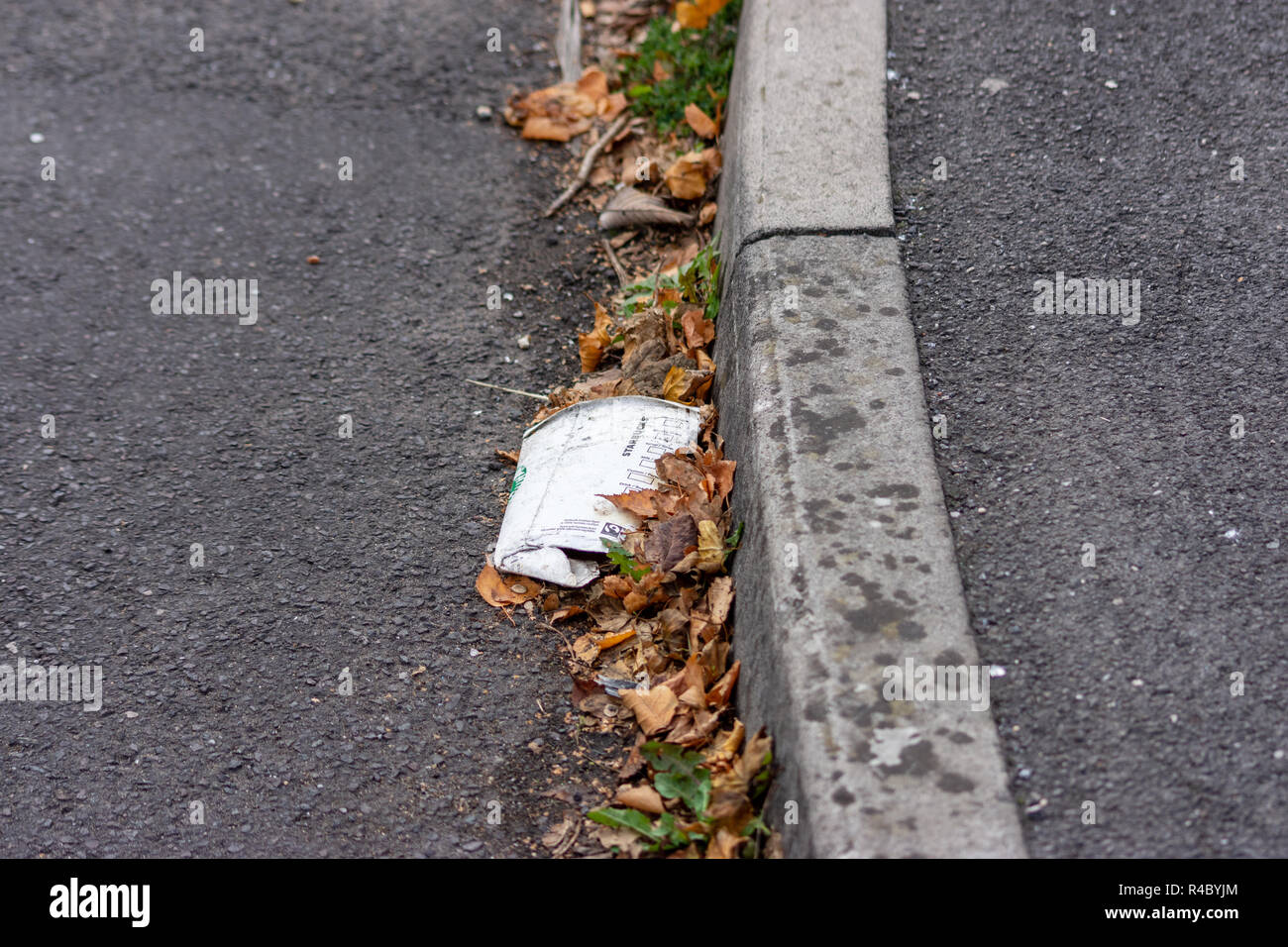 A flattened crushed discarded Starbucks cardboard takeaway cup that has been dropped as litter by the pavement kerbstones at the side of the road - Stock Image