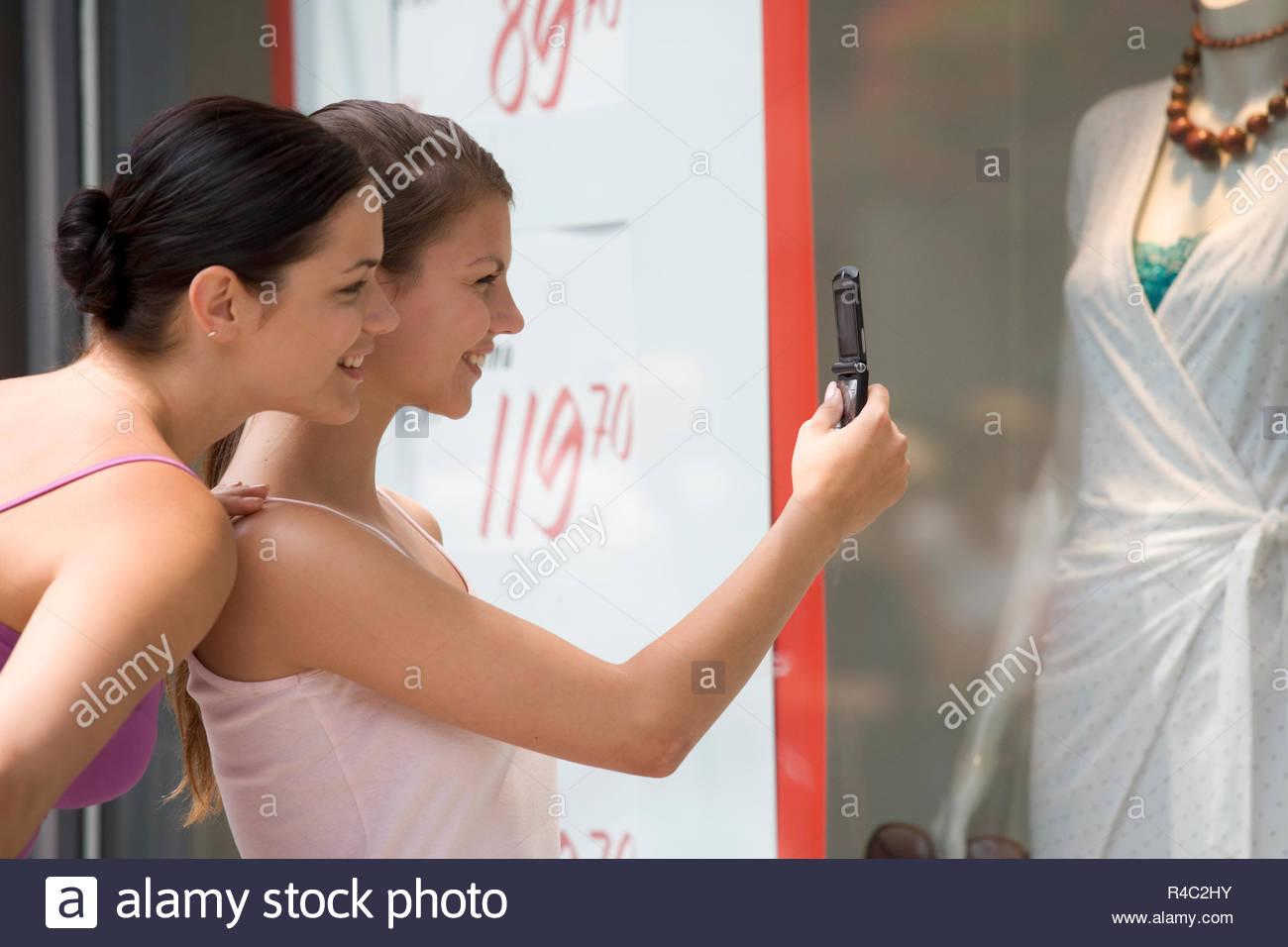 Two young women looking in a shop window - Stock Image