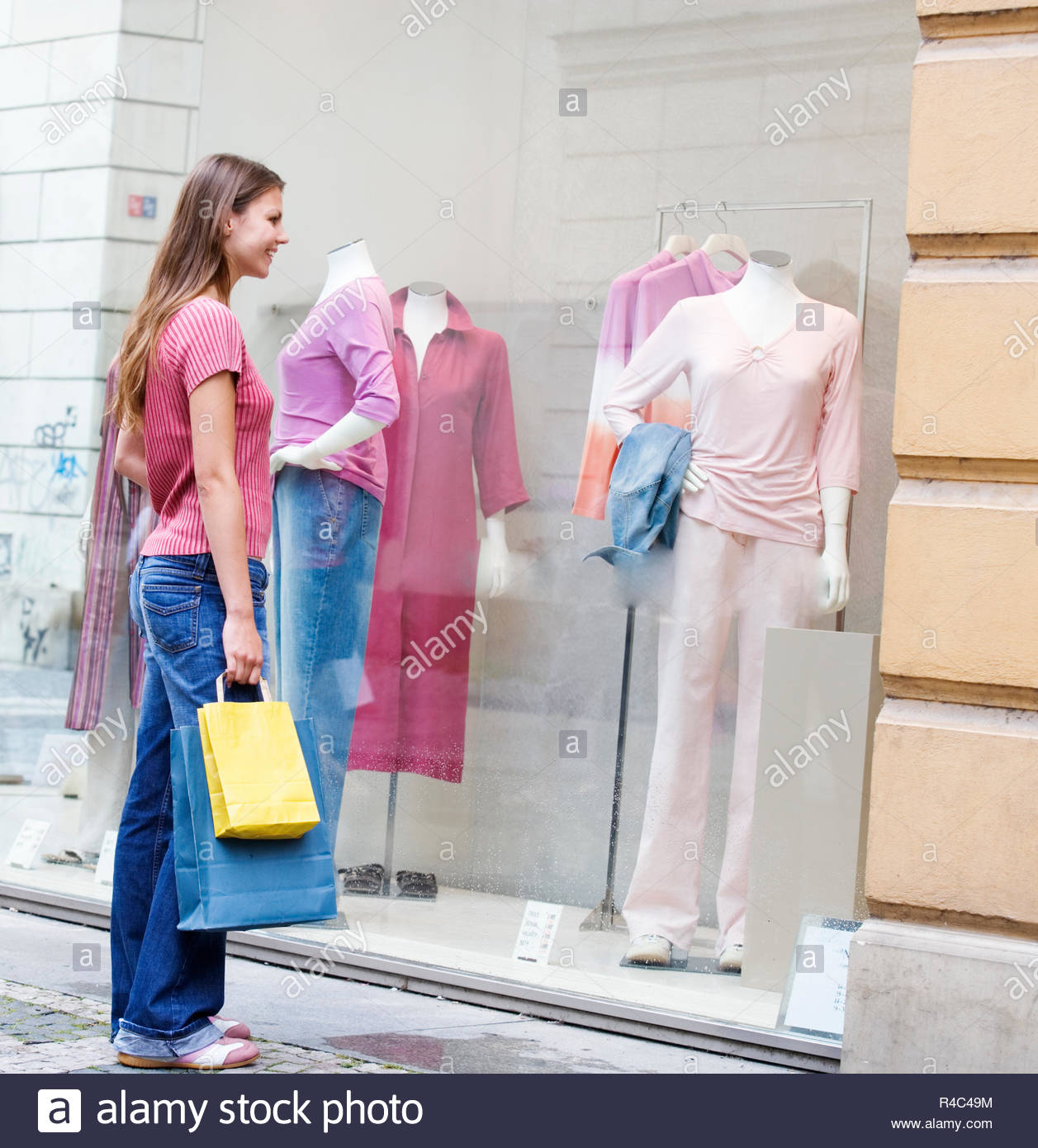 A young woman looking in a shop window - Stock Image