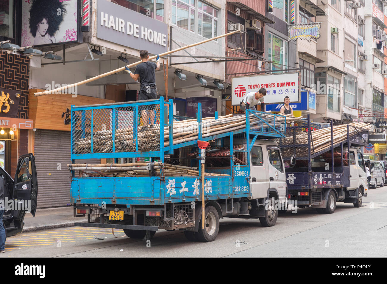 KOWLOON, HONG KONG - APRIL 21, 2017: Workers Unloading Trucks With Bamboo Scaffoldings at Construction Site at Mong Kok in Kowloon, Hong Kong. - Stock Image