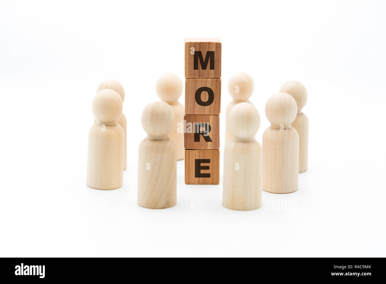 Wooden figures as business team in circle around word MORE, isolated on white background, minimalist concept - Stock Image